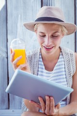 Pretty blonde woman using her tablet and holding orange juice