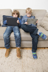 Two boys playing video games on a tablet computer