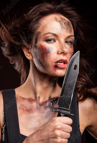 Poster Attractive girl in sexy military uniform holding a knife
