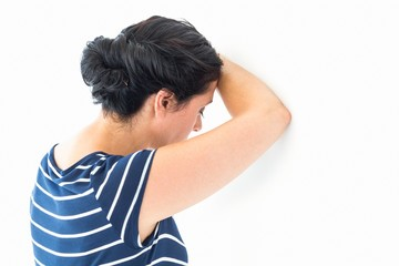 Sad woman leaning against the wall