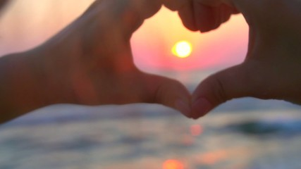 Girl making heart with her hands over sea background