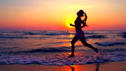 Young woman jogging along the sea coast over sunset