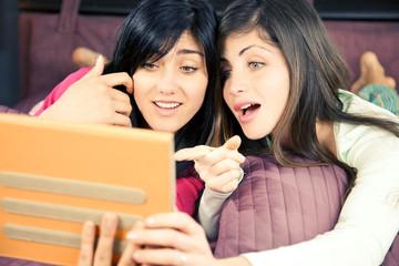 Girls surprised reading social network on tablet