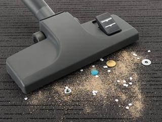 Staubsaugerdüse und Schmutz auf Teppich