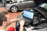 KFZ Mechaniker liest mit Diagnosecomputer Fehlerspeicher aus