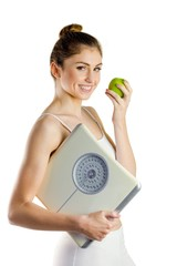Slim woman holding scales and apple