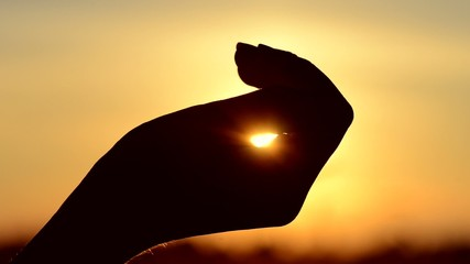Hand catching a sun against beautiful sunset