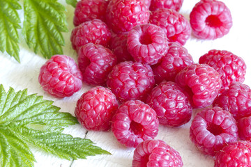 Raspberry with green leaves on white background closeup