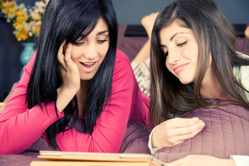 Two girls smiling reading news on tablet on social network