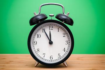 Black alarm clock against green background