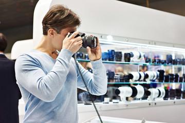 Man photographer tests digital SLR camera in shop