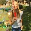 Frau macht Seifenblasen im Park