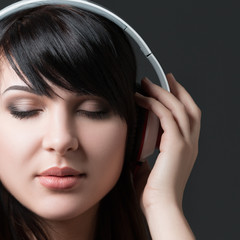 Close-up portrait of young woman listening to music