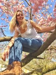 Frau sitzt in Kirschbaum im Frühling