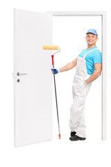 Painter holding a paint roller and leaning on a door