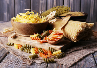 Different types of pasta on sackcloth on wooden background