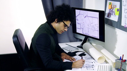 Cool handsome architect working on project in office