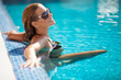 Beautiful woman in black bikini relaxing in the swimming pool - 82045262