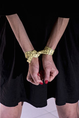 Hands of a woman tied with measure tape
