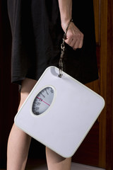 Anorexic woman handcuffed to a bathroom scale
