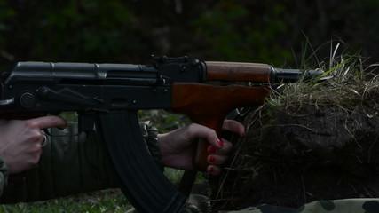 Woman firing AK 47 assault rifle, painted nails  on trigger