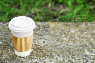 Paper cup on gray stone, outdoors