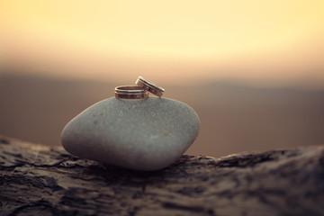 Wedding rings lie on the sea stone.