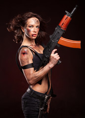 Beautiful young woman holding an automatic assault rifle.