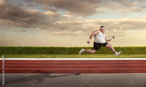 Funny overweight man speeding on the running track with copy spa - 82048890
