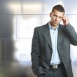Young unsure businessman standing in front of wall