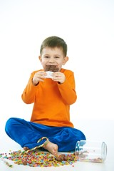 Joyous kid eating chocolate sitting cross-legged