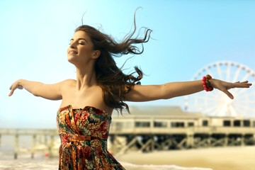 Young woman eyes closed arms wide open at beach