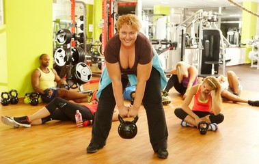 Determined fat woman training in health club