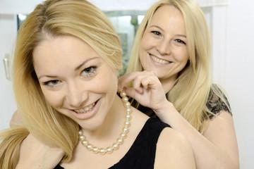 Frau legt Freundin Perlenkette an