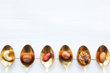 Nuts in spoon on white wooden table