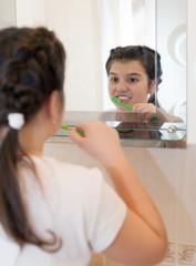 girl brushing her teeth in   bathroom.