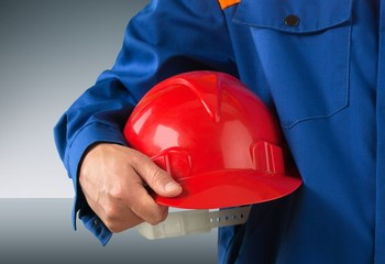 Site. Worker holding a helmet with background of  blurred