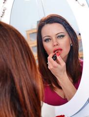 Mujer maquillandose,pintando labios en tocador,espejo.