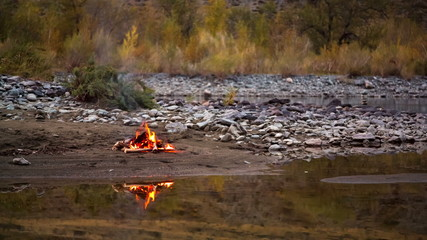 Camp fire on the river bank in the mountains
