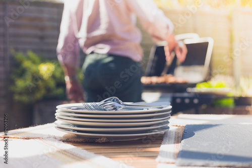 Plates on a table outside with man in background - 82053216