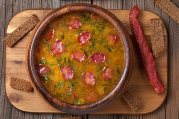 Beer soup with sausage croutons and beer on vintage wooden backg