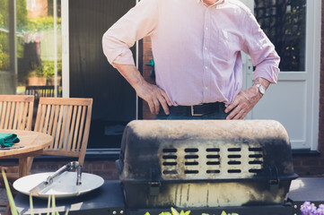 Senior man doing barbecue in garden