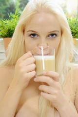 Frau trinkt Kaffee mit Milchschaum