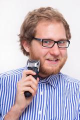 Bearded man with an electric razor