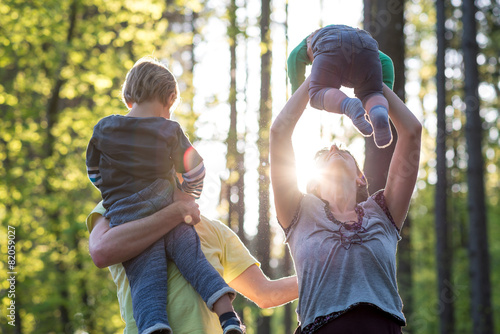 Parents playing with their two young children - 82059027