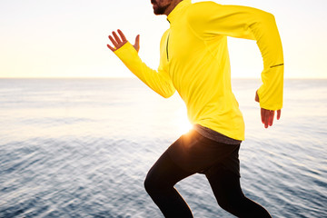 Sport fitness runner running outside at sunset at beach near dee