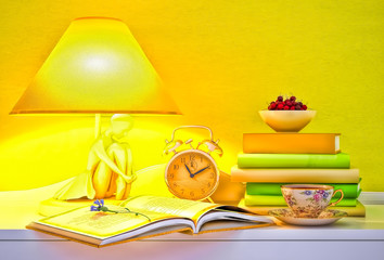 Lamp, books, hours, cup of tea, plate of cherry.