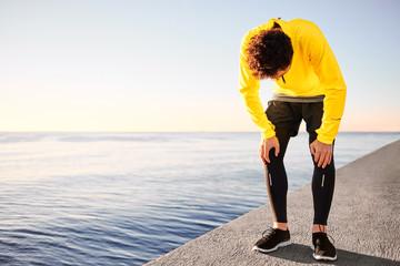 Workout outdoor runner. Man running taking a break from run outs