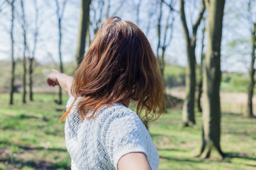 Woman pointing in forest