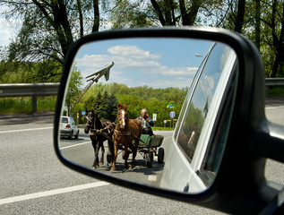 Horse carriage ahead of the car.